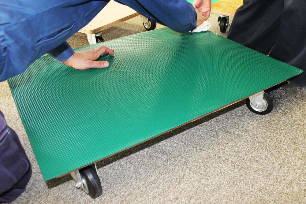 接着作業はゴムと台車の間に空気が入らないように、二人一組で丁寧に貼り付けていきます