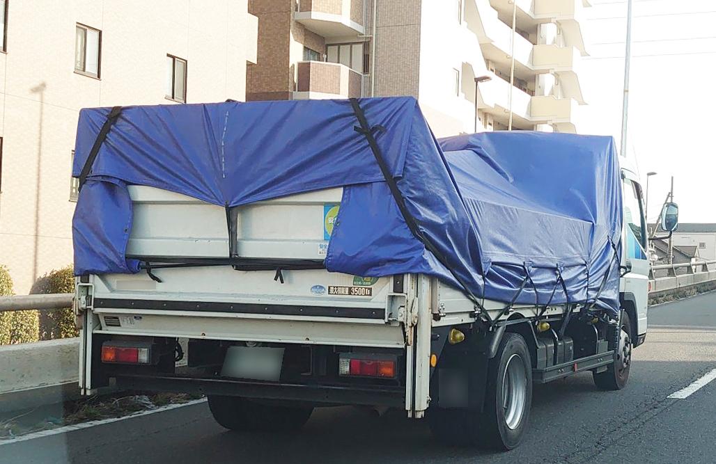 マルイチブルーのトラックシートを装着した中型トラック