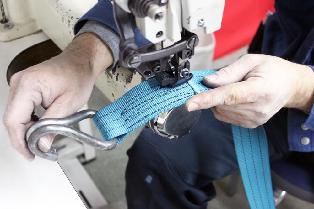 新品のベルトに金具やバックルを取り付けて縫製します